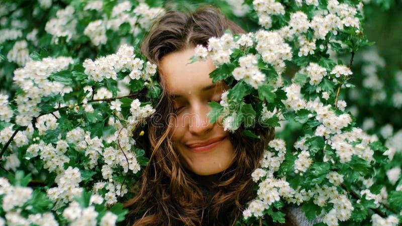 Jeune femme aux yeux verts de sourire heureuse avec des fleurs Beauté normale photos libres de droits