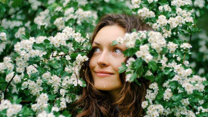 Jeune femme aux yeux verts de sourire heureuse avec des fleurs Beauté normale images stock