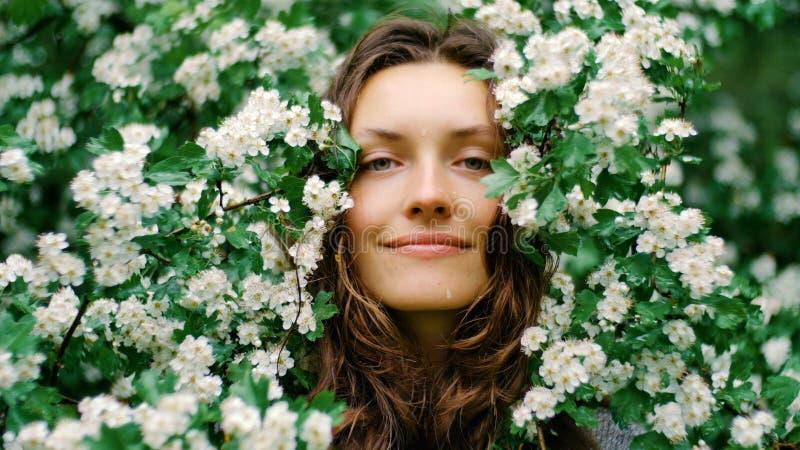 Jeune femme aux yeux verts de sourire heureuse avec des fleurs Beauté normale photos stock