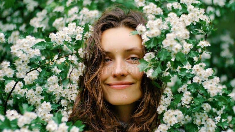 Jeune femme aux yeux verts de sourire heureuse avec des fleurs regardant l'appareil-photo Beauté normale photo libre de droits
