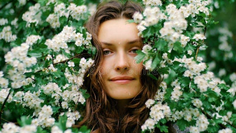 Jeune femme aux yeux verts de sourire heureuse avec des fleurs regardant l'appareil-photo Beauté normale photos libres de droits