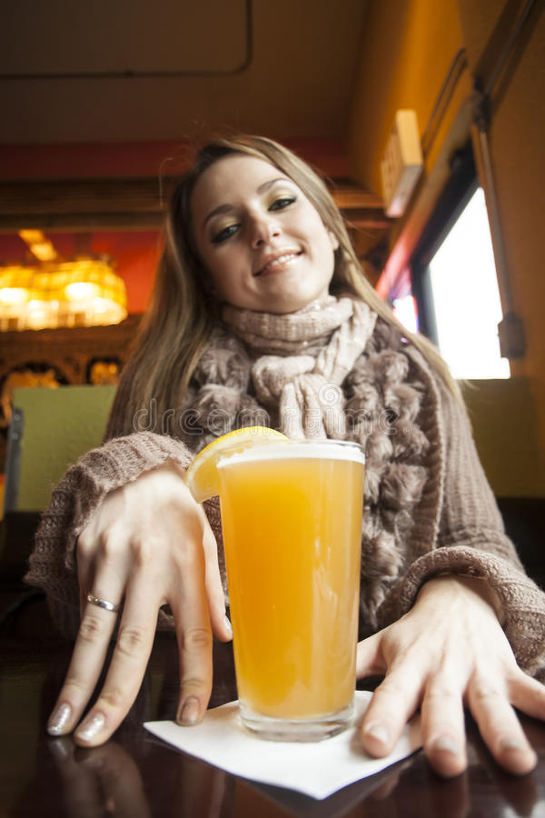 Jeune femme avec de beaux yeux bleus buvant de la bière de Hefeweizen photos libres de droits