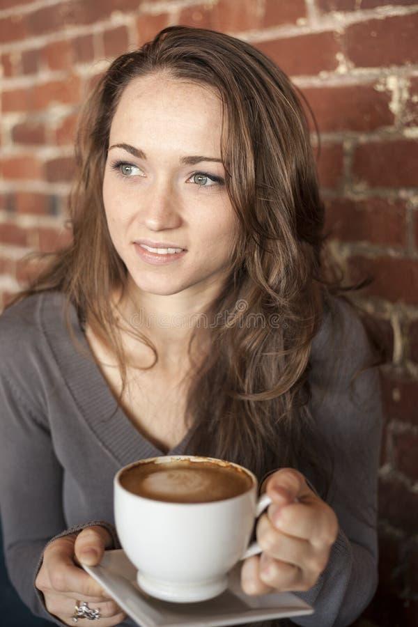 Jeune femme avec de beaux yeux verts avec la tasse de café blanc photographie stock libre de droits
