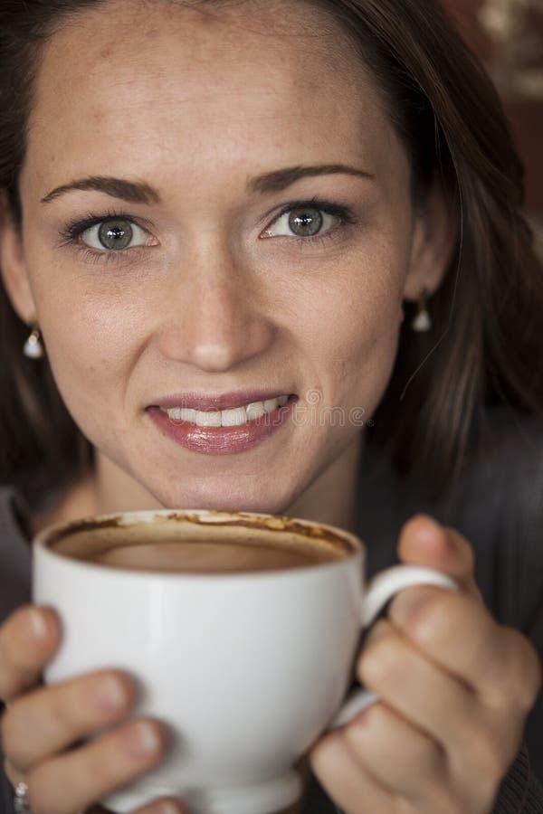 Jeune femme avec de beaux yeux verts avec la tasse de café blanc images stock