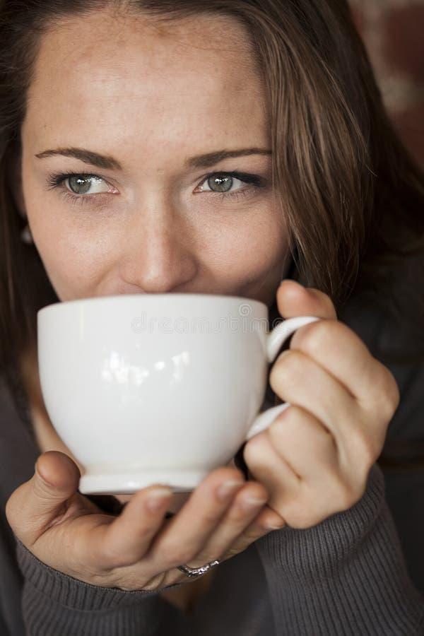 Jeune femme avec de beaux yeux verts avec la tasse de café blanc image libre de droits