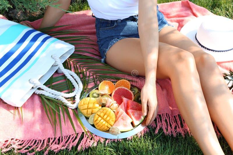 Jeune femme avec de divers fruits délicieux sur le pique-nique d'été en parc photos stock