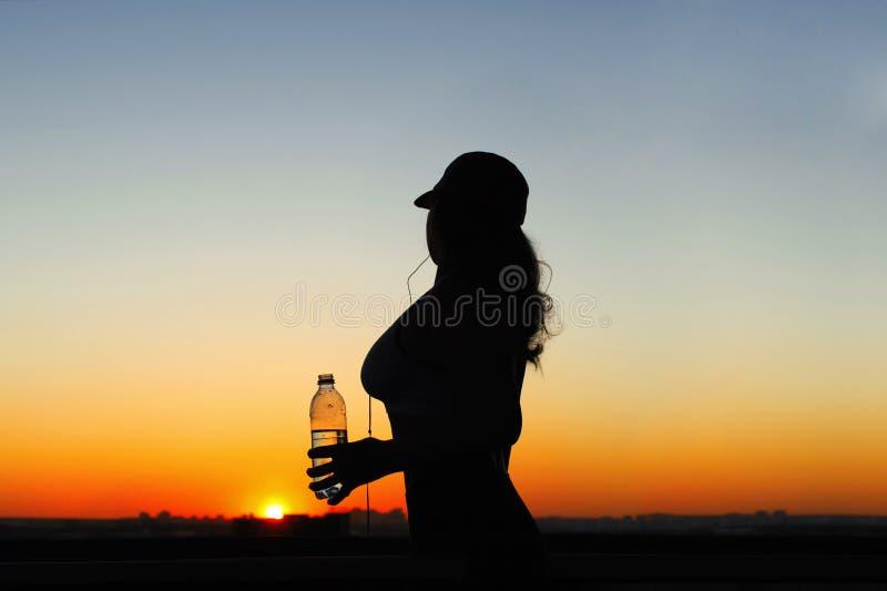 Jeune femme avec de l'eau bouteille après avoir pulsé sur les milieux de coucher du soleil Vue supérieure sur la ville images stock