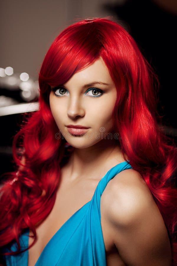 Jeune femme avec de longs beaux cheveux rouges luxueux dans un bleu FLB images stock