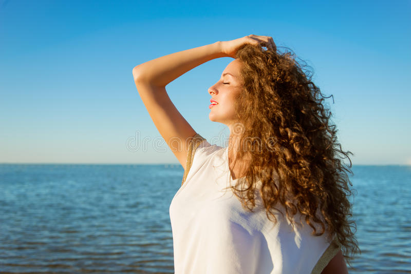 Jeune femme avec de longs cheveux bouclés et yeux fermés sur la plage image libre de droits