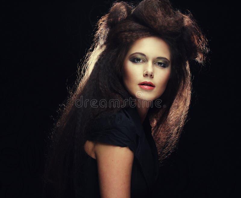 Jeune femme avec de longs cheveux bruns colorés et maquillage lumineux photo stock