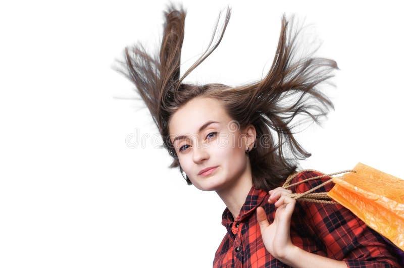 Jeune femme avec de longs cheveux de soufflement et sacs shoping image libre de droits