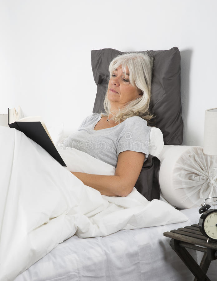 Jeune femme avec de longs cheveux se reposant dans la lecture de siège fenêtre photo stock
