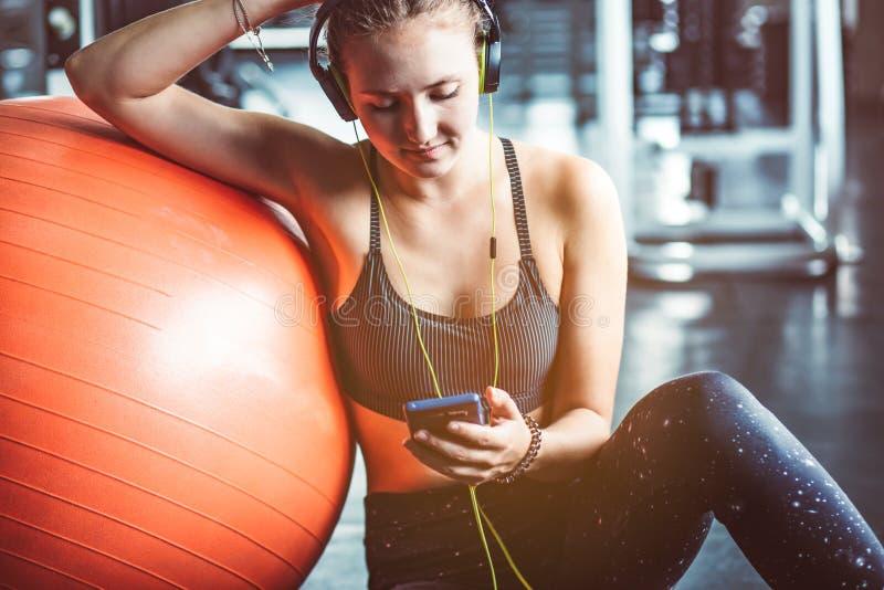 Jeune femme avec des écouteurs écoutant la musique après séance d'entraînement dure photo stock