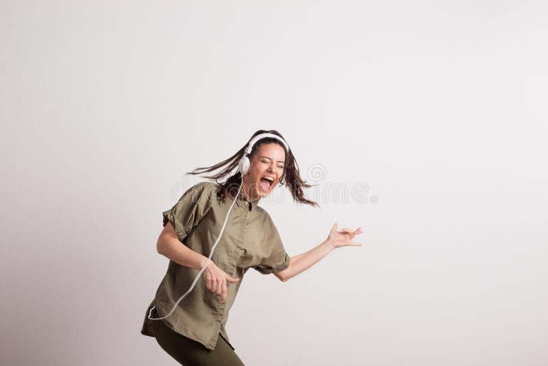 Jeune femme avec des écouteurs, écoutant la musique, chantant et feignant pour jouer la guitare images libres de droits
