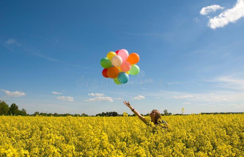 Jeune femme avec des ballons sur la zone de canola. images libres de droits
