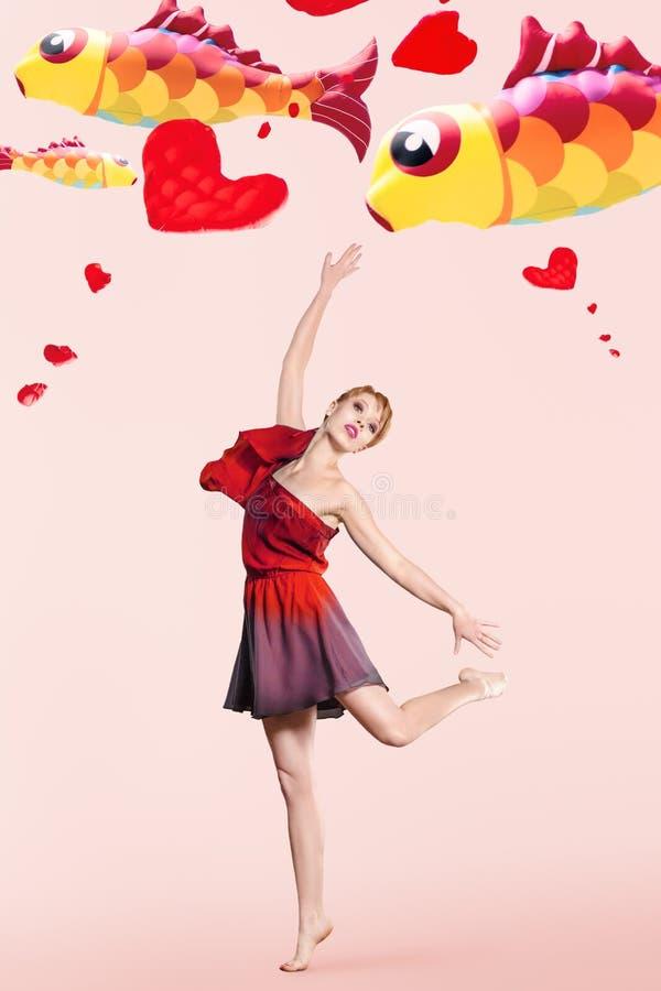 Jeune femme avec des cerfs-volants de vol derrière images stock