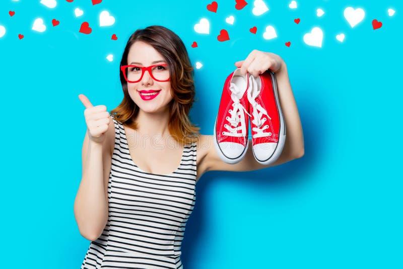 Jeune femme avec des chaussures en caoutchouc et des coeurs abstraits photographie stock