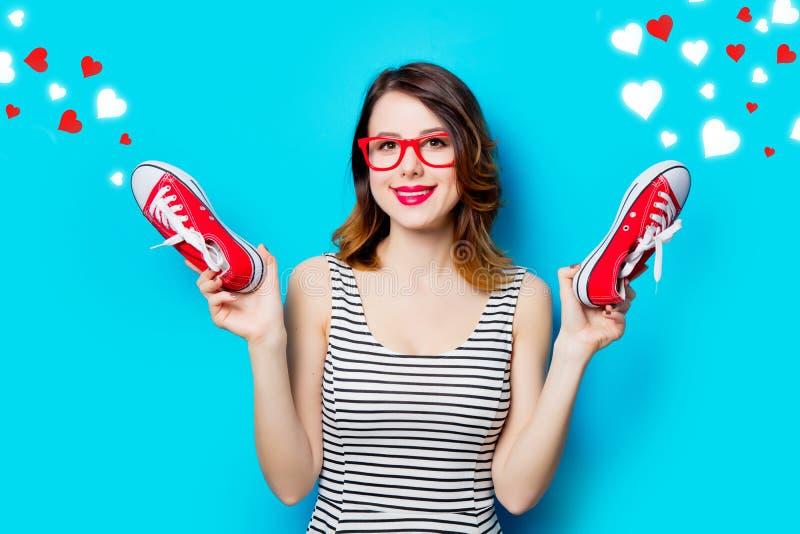 Jeune femme avec des chaussures en caoutchouc et des coeurs abstraits photographie stock libre de droits