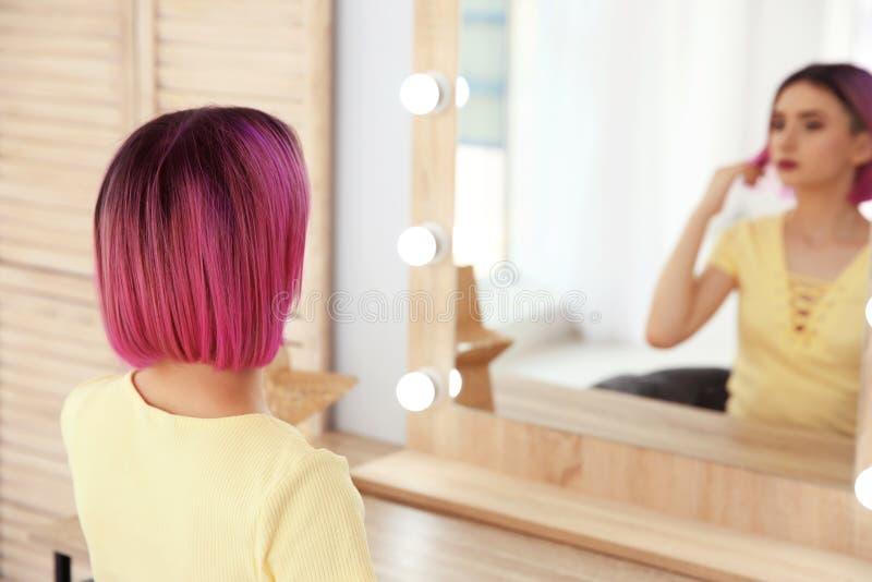 Jeune femme avec des cheveux de couleur regardant dans le miroir photographie stock libre de droits