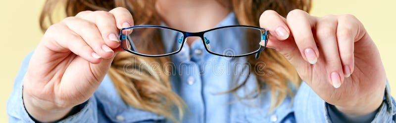 Jeune femme avec des cheveux de gingembre tenant des verres de lecture devant elle Jeune femme avec des lunettes sur le fond jaun photos stock