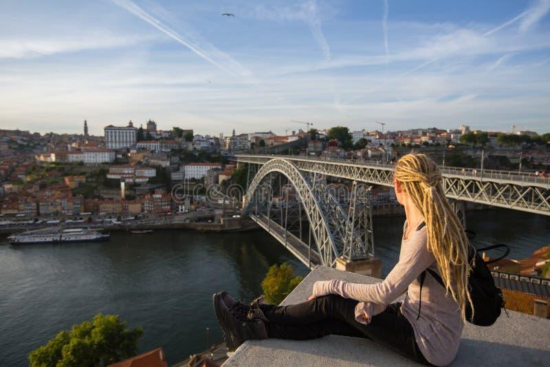 Jeune femme avec des dreadlocks sur le point de vue vis-à-vis du pont et de Ribeira de Dom Luis I sur la rivière de Douro, Porto photos libres de droits