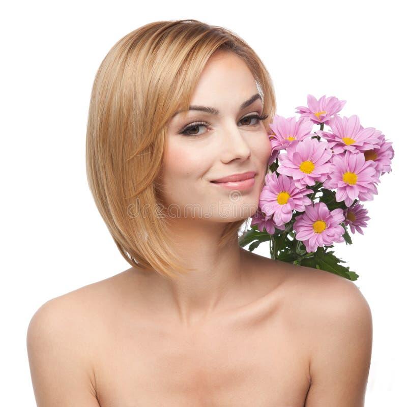 Jeune femme avec des fleurs à côté de son visage photographie stock libre de droits