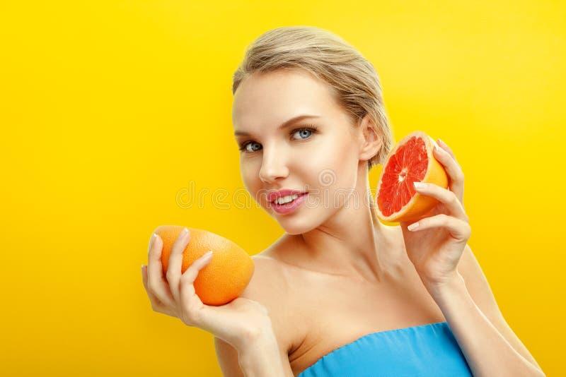 Jeune femme avec des fruits sur le fond orange lumineux image stock