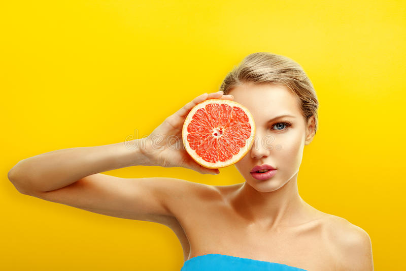 Jeune femme avec des fruits sur le fond orange lumineux image libre de droits