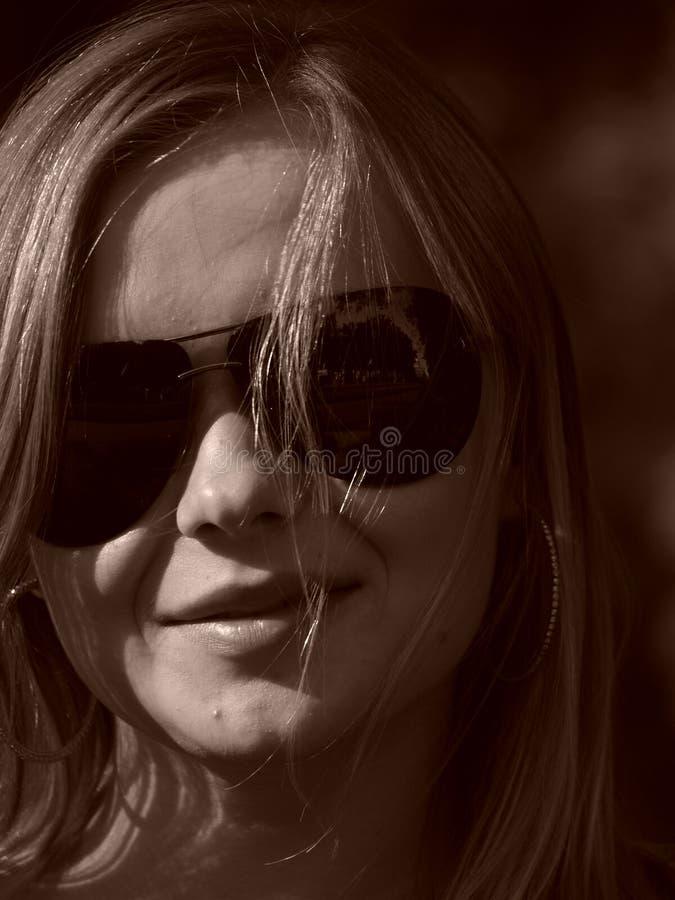 Jeune femme avec des glaces de soleil dans la sépia photos stock