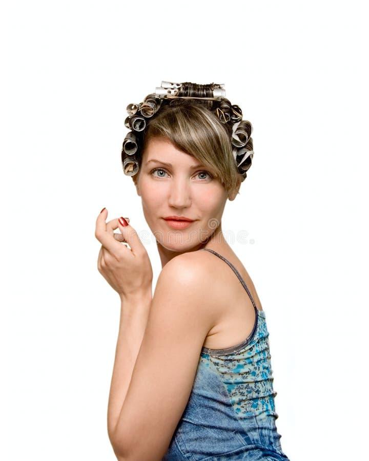Jeune femme avec des haircurlers dans son héritier images stock