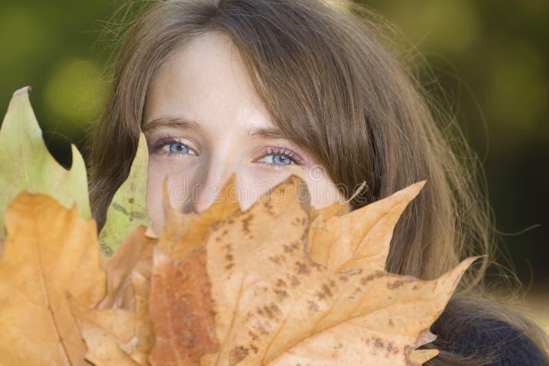 Jeune femme avec des lames d'automne photographie stock