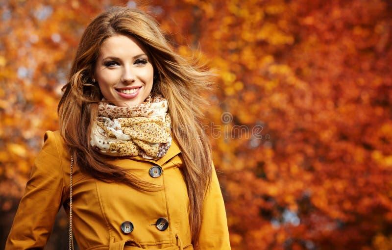 Jeune femme avec des lames d'automne photographie stock libre de droits