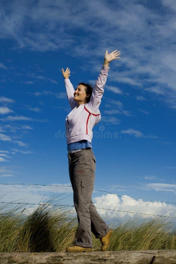 Jeune femme avec des mains dans le ciel photo stock