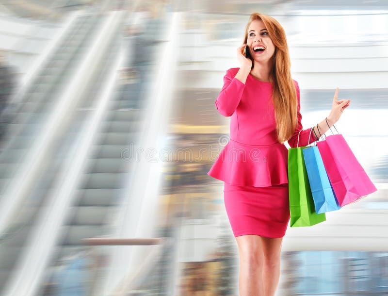 Jeune femme avec des paniers au centre commercial image stock