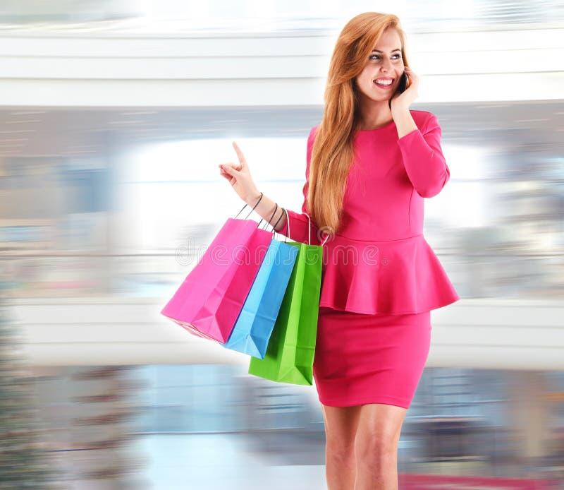 Jeune femme avec des paniers au centre commercial image libre de droits