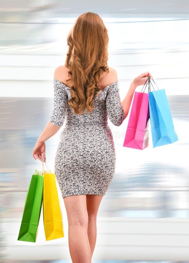Jeune femme avec des paniers au centre commercial photo stock