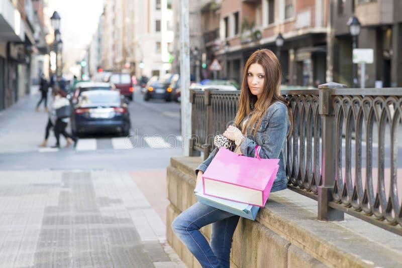 Jeune femme avec des paniers se reposant dans la rue. images stock