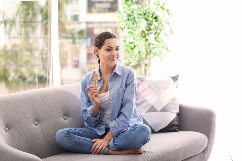 Jeune femme avec des pilules contraceptives à la maison photo stock