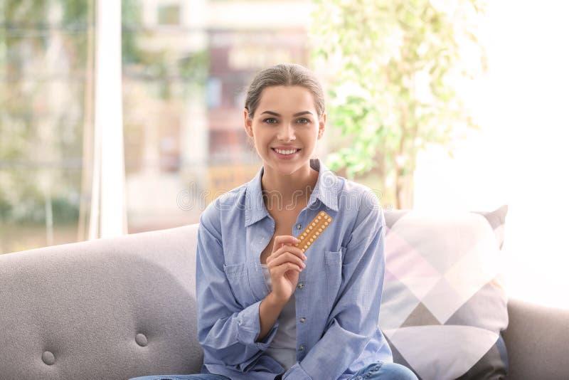 Jeune femme avec des pilules contraceptives à la maison images stock