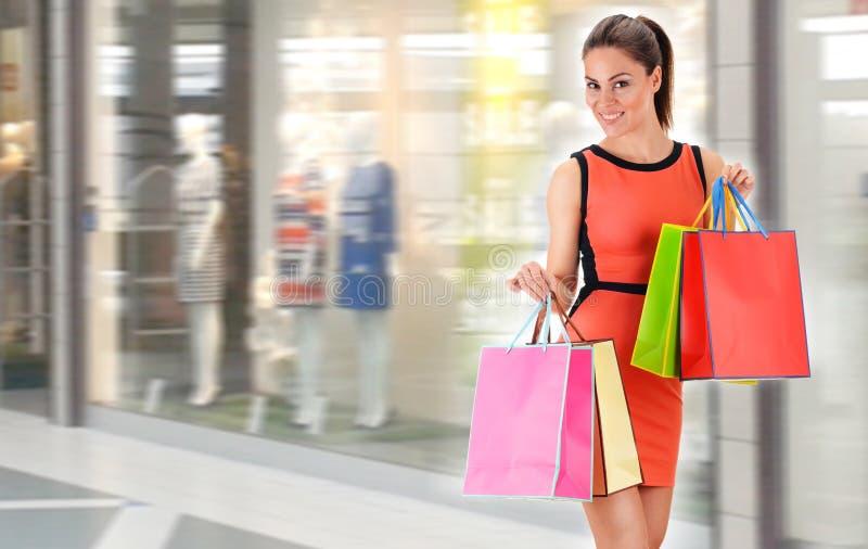 Jeune femme avec des sacs dans le centre commercial images libres de droits