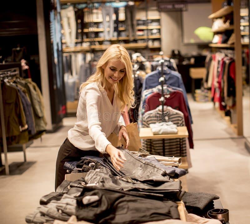 Jeune femme avec des sacs ? provisions se tenant au magasin d'habillement photos libres de droits