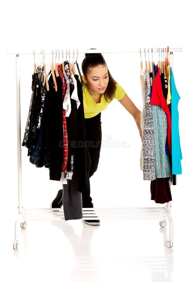 Jeune femme avec des vêtements sur le cintre photographie stock