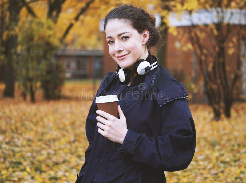 Jeune femme avec du café à aller mettre en forme de tasse et des écouteurs en automne images libres de droits