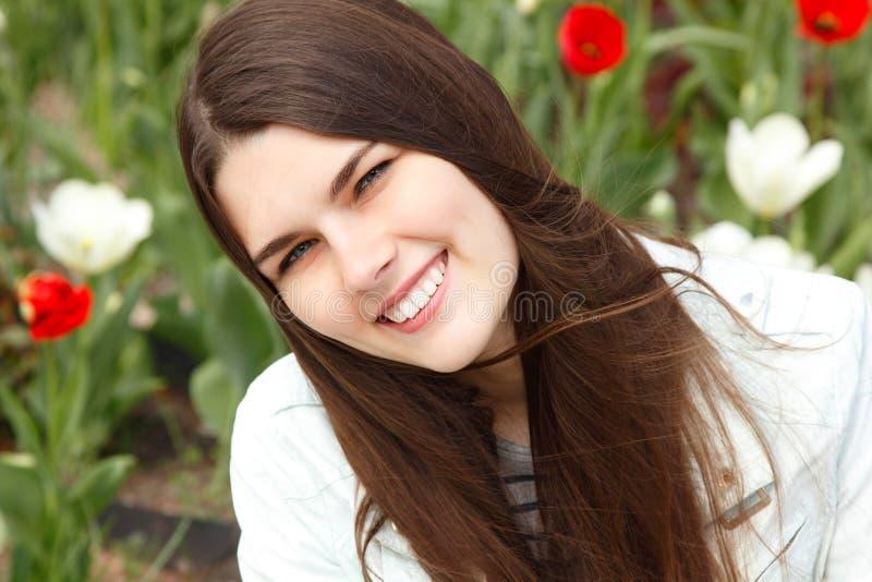 Jeune femme avec du charme au-dessus du ressort extérieur avec des tulipes photographie stock libre de droits