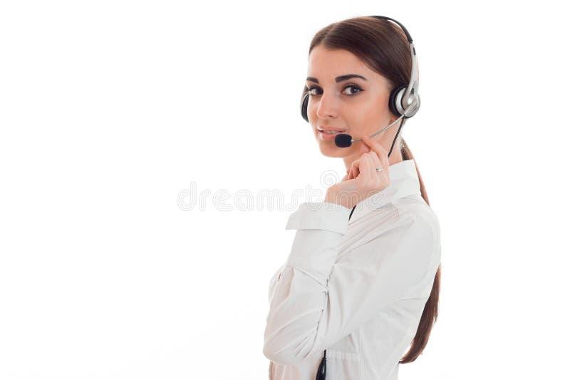Jeune femme avec du charme d'affaires dans l'uniforme avec les écouteurs et le microphone regardant l'appareil-photo et le sourir photo stock