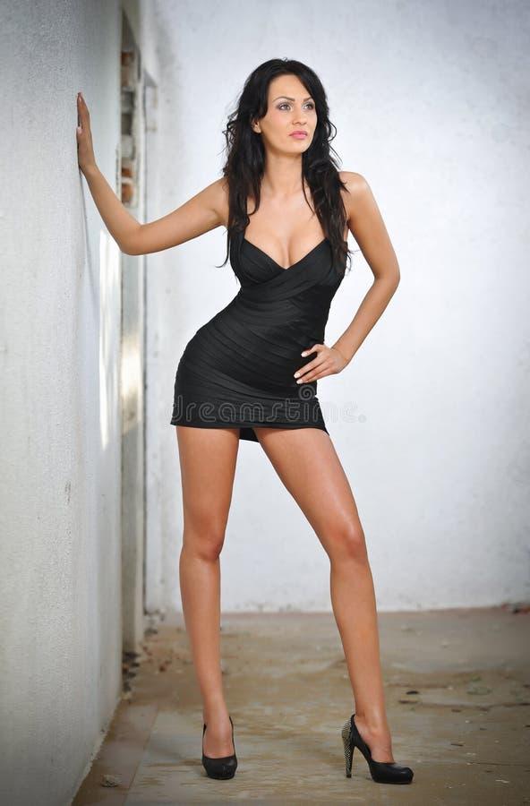 Jeune femme avec du charme de brune dans la robe serrée noire d'ajustement posant contre un mur images libres de droits