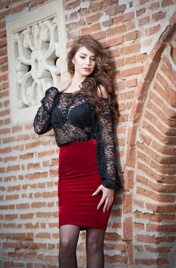 jeune femme avec du charme de brune dans le chemisier noir de dentelle  la jupe rouge et des