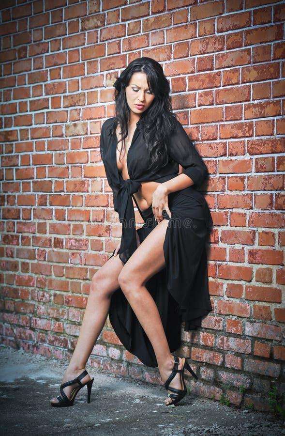 Jeune femme avec du charme de brune dans le noir et talons hauts restant près d'un mur de briques rouge image libre de droits