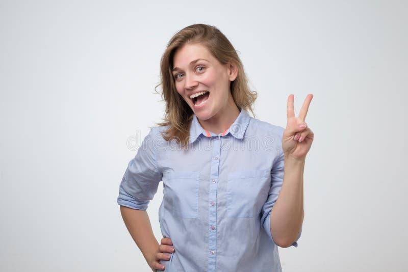 Jeune femme avec du charme de sourire dans la chemise bleue montrant des sig de paix photo libre de droits