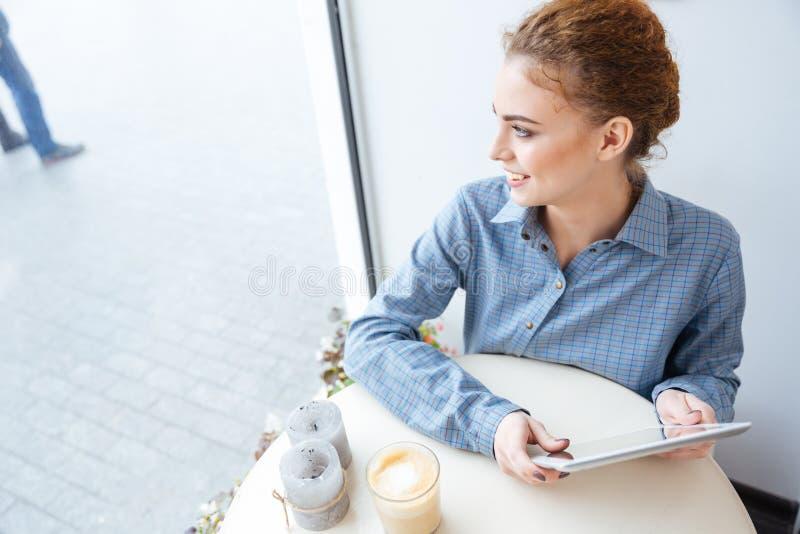 Jeune femme avec du charme gaie à l'aide du comprimé en café photo stock